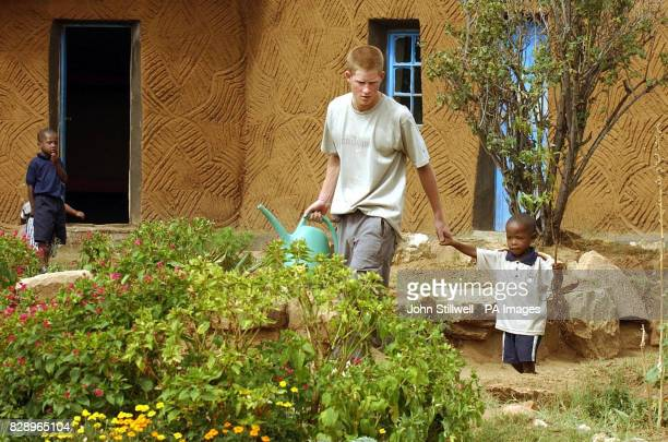 Prince Harry the younger son of Britain's Prince Charles leads young orphan Mutsu Potsane to plant a peach tree together at the Mants'ase Children's...