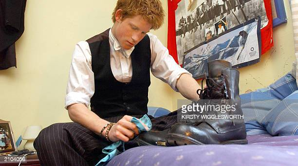 Prince Harry the younger son of the Prince of Wales who finishes his studies at Eton College later this month polishes his boots that he wears while...