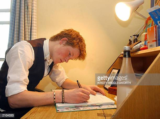 Prince Harry the younger son of the Prince of Wales works 12 May 2003 in his room at Eton College AFP/POOL PHOTO KIRSTY WIGGLESWORTH