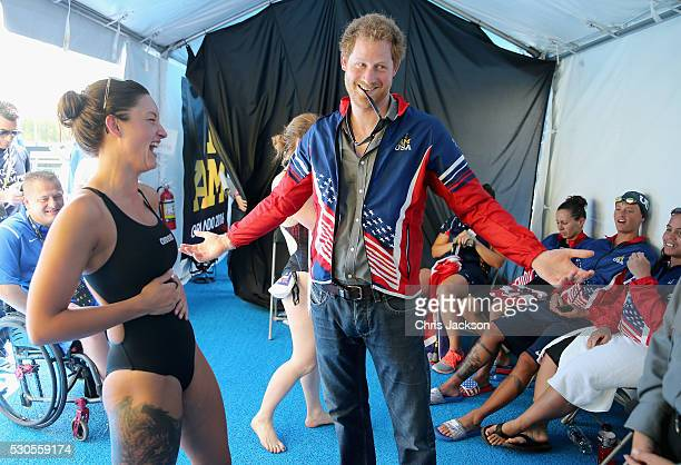 Prince Harry tries on USA Invictus Team Member Elizabeth Marks's Team USA jersey in the competitor's tent at the swimming pool during the Invictus...