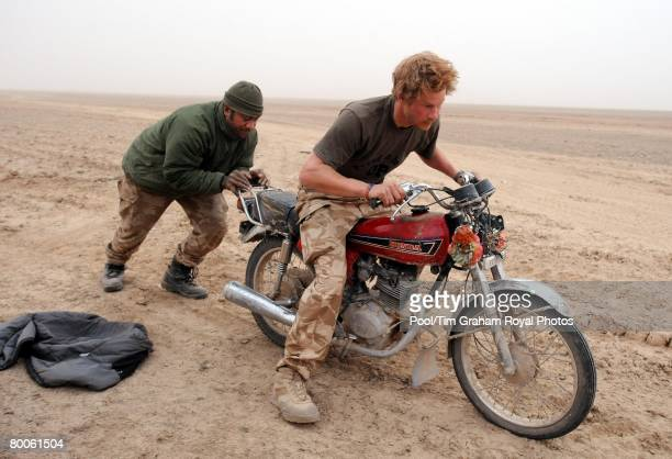 Prince Harry tries to push start an abandoned motorcycle in the desert with the help of 'Max' his Fijian tank driver on February 21 2008 in Helmand...
