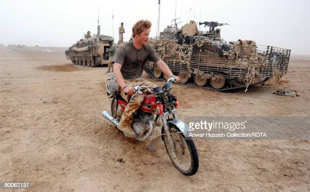 Prince Harry tries to start an abandoned motorcycle in the desert on February 21 2008 in Helmand Province Afghanistan