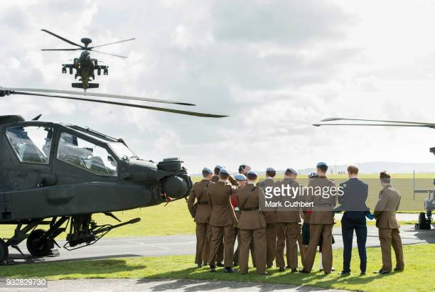 Prince Harry watches an Apache Helicopter flypast after presenting 12 pilots from Course 17/02 of the Army Air Corps with their Wings during a...