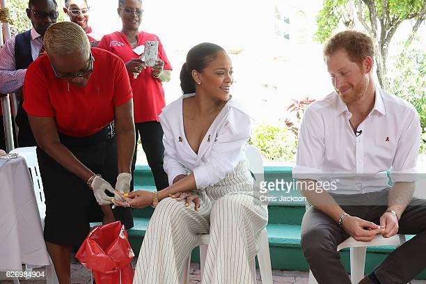 Prince Harry watches as Singer Rihanna gets her blood sample taken for an live HIV test in order to promote more widespread testing for the public at...