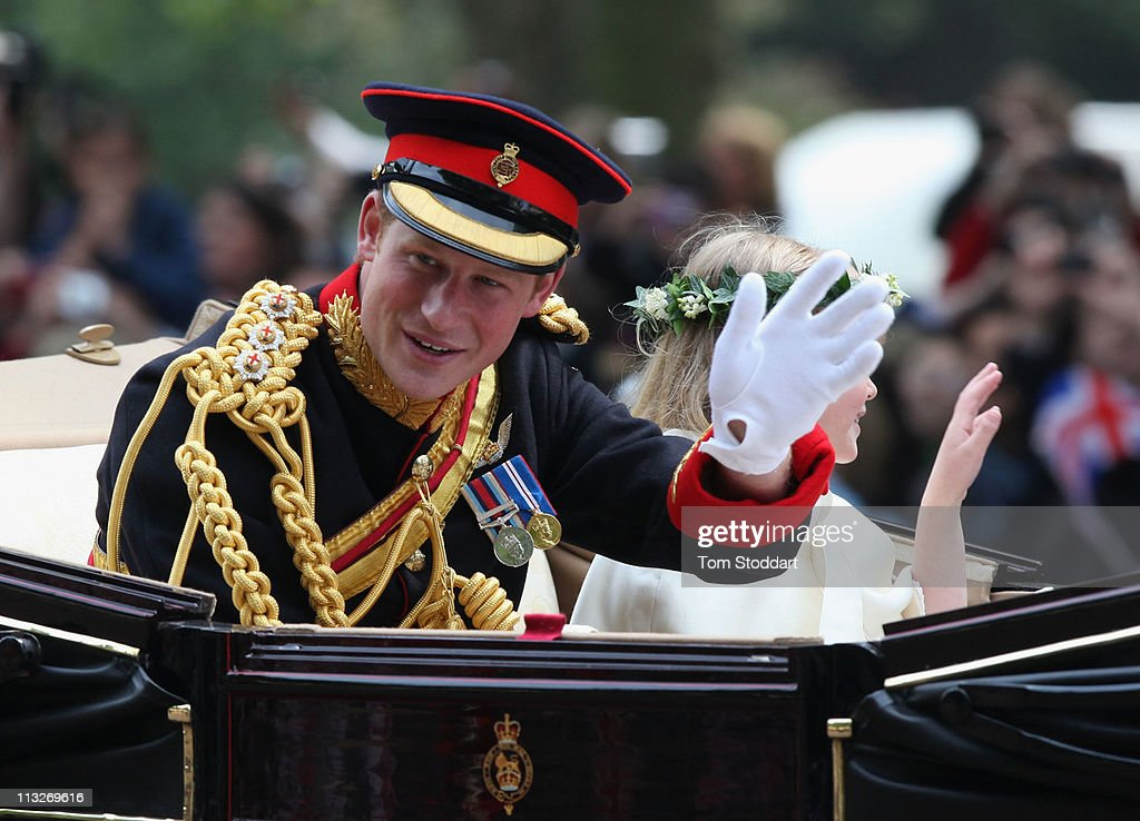 Prince Harry waves to the crowd as he makes the journey by carriage procession to Buckingham Palace following their marriage at Westminster Abbey on April 29, 2011 in London, England. The marriage of the second in line to the British throne was led by the Archbishop of Canterbury and was attended by 1900 guests, including foreign Royal family members and heads of state. Thousands of well-wishers from around the world have also flocked to London to witness the spectacle and pageantry of the Royal Wedding.