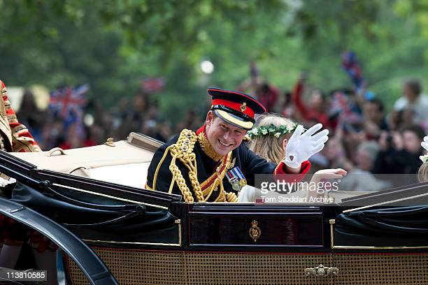 Prince Harry waves to the crowd as he makes the journey by carriage in procession to Buckingham Palace following the wedding of Prince William and...