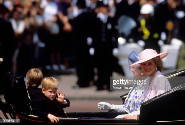 Prince Harry waves to the crowds as he travels in an open carriage with Diana Princess of Wales Queen Elizabeth the Queen Mother and Prince William...