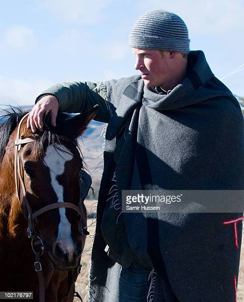 Prince Harry wearing a blanket to keep out the cold strokes his horse as he arrives at the Semongkong Children's Centre on June 17 2010 in Semongkong...