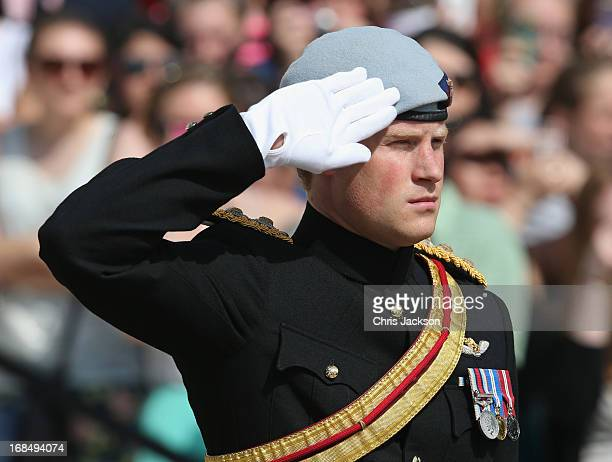 Prince Harry wearing his No 1 ceremonial uniform of The Blues and Royals salutes as he pays his respects to the victims of the Afghanistan conflict...