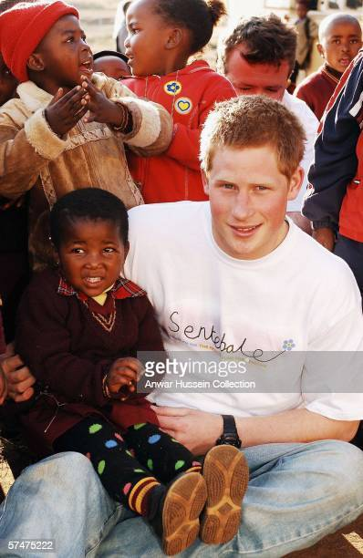 Prince Harry wears a shirt with the Sentebale logo as he holds a small girl while on visit to the Good Shepherd home while on a return visit to...