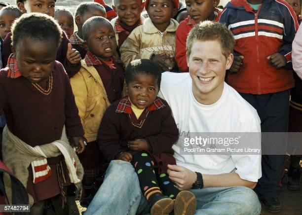 Prince Harry wears a shirt with the 'Sentebale' logo as he meets young children on visit to the Good Shepherd home on a return visit to Lesotho in...