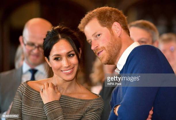 Prince Harry whispers to Meghan Markle as they watch a dance performance by Jukebox Collective in the banqueting hall during a visit to Cardiff...