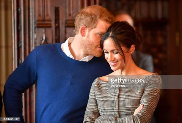 Prince Harry whispers to Meghan Markle as they watch a performance by a Welsh choir in the banqueting hall during a visit to Cardiff Castle on...