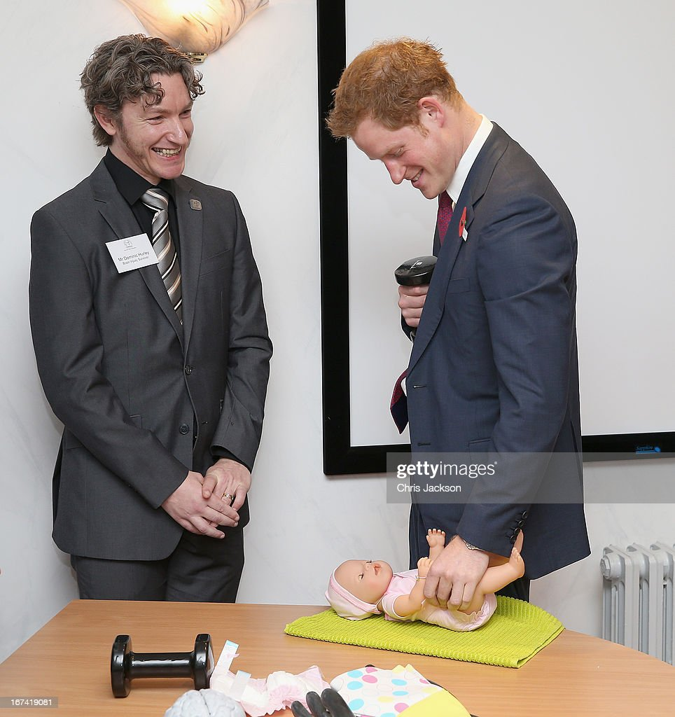 Prince Harry (R) with brain injury survivor Dominic Hurley as he attempts to change a nappy with one hand to simulate what it would be like if he had a brain injury during a visit to Headway, the brain injury association at Bradbury House during an official visit to Nottingham on April 25, 2013 in Nottingham, England.