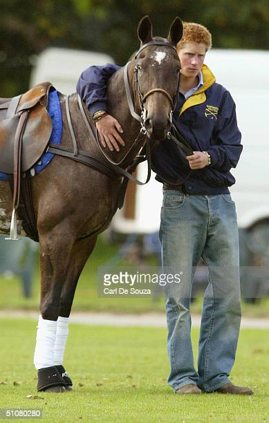 Prince Harry with his arm around the neck of a pony at Cirencester Polo Club Gloucestershire on July 18 2004