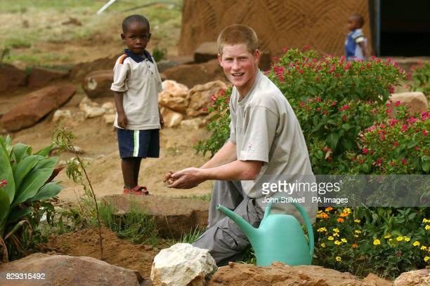 Prince Harry with young orphan Mutsu Potsane at the Mants'ase Children's Home for children orphaned by and suffering from Aids near Mohale's Hoek...