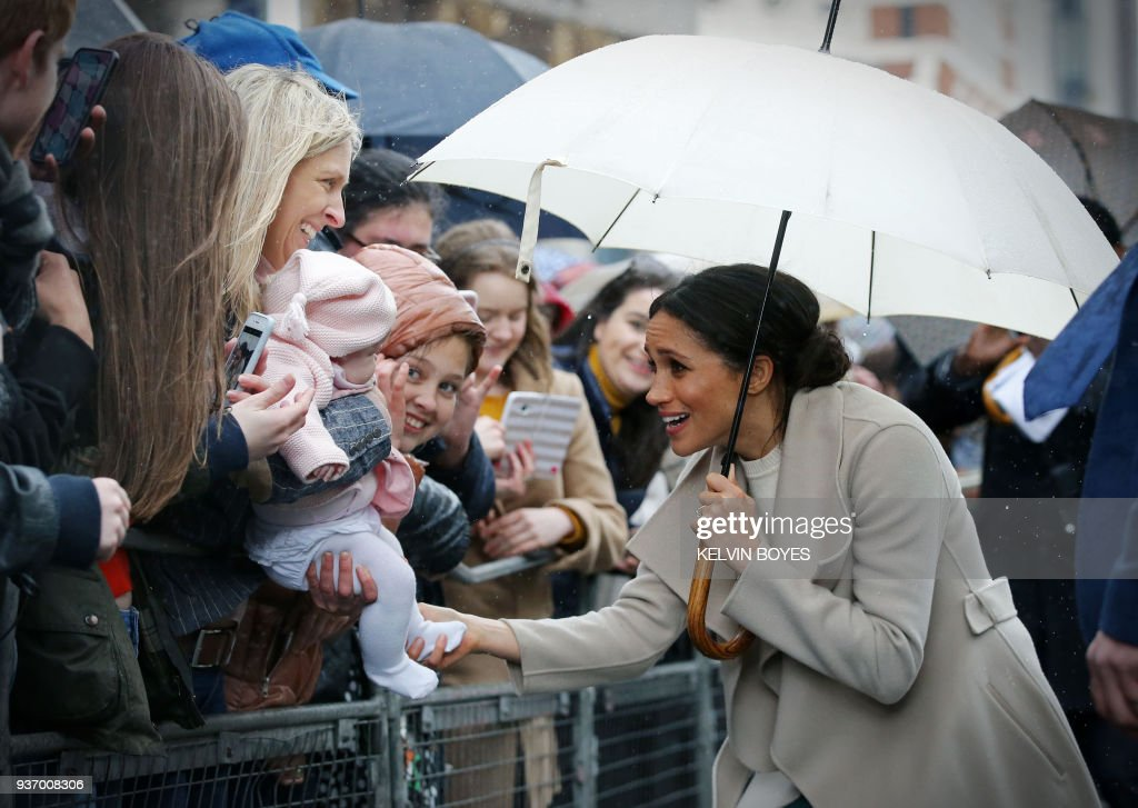 Prince Harry's fiancee, US actress Meghan Markle plays with a baby as she greet well-wishers after a visit to one of Belfast's most historic buildings, The Crown Liquor Saloon, a former Victorian gin palace, now run by the National Trust, on March 23, 2018, during the Royal Couple's first joint visit to Northern Ireland.