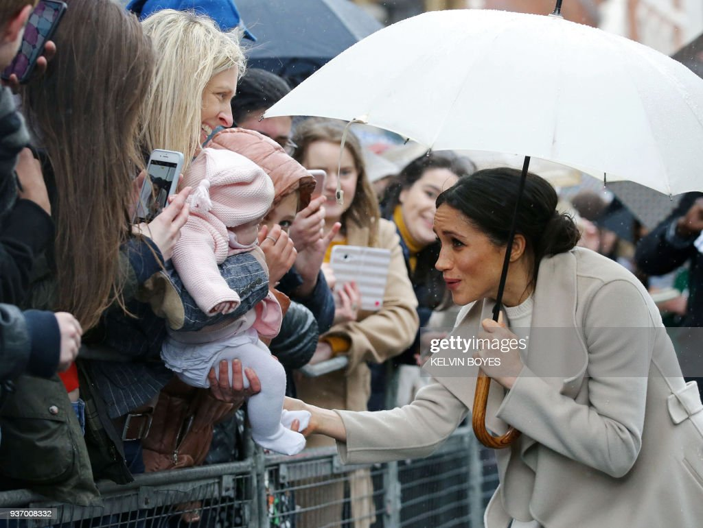 Prince Harry's fiancee, US actress Meghan Markle plays with a baby as she greet well-wishers after a visit to one of Belfast's most historic buildings, The Crown Liquor Saloon, a former Victorian gin palace, now run by the National Trust, on March 23, 2018, during the Royal Couple's first joint visit to Northern Ireland. / AFP PHOTO / POOL / Kelvin BOYES