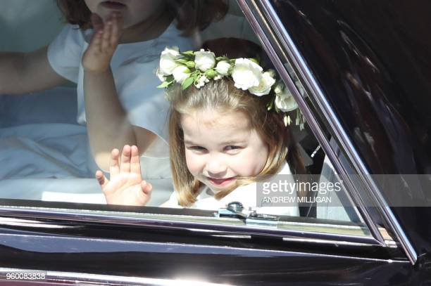 TOPSHOT Prince Harry's niece and bridesmaid Princess Charlotte waves as she arrives for the wedding ceremony of Britain's Prince Harry Duke of Sussex...