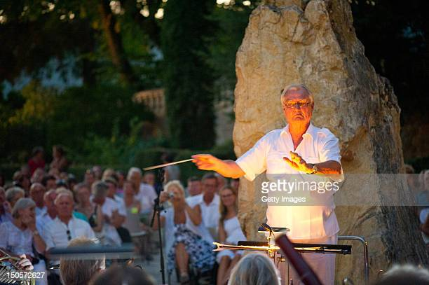 Prince Henrik of Denmark conducts the band during a summer concert with the Royal Guards Band in the park at the Chateau de Cayx on August 21 in...