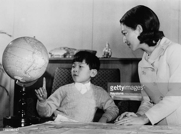 Prince Hiro aka Crown Prince Naruhito of Japan studying a globe with his mother Empress Michiko at Togu Palace in Tokyo February 1968 The globe was...