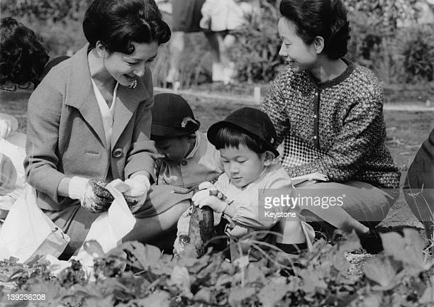 Prince Hiro aka Prince Naruhito of Japan helps his mother Crown Princess Michiko dig up sweet potatoes at a farm during a school excursion to the...