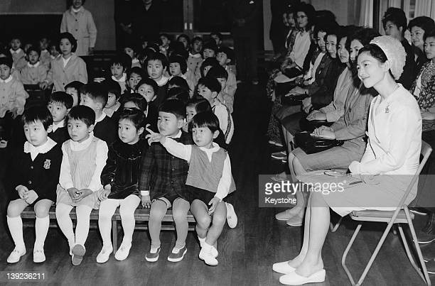 Prince Hiro, aka Prince Naruhito of Japan, watches a Doll Festival performance at Gakushuin Kindergarten in Tokyo, with his mother, Crown Princess...