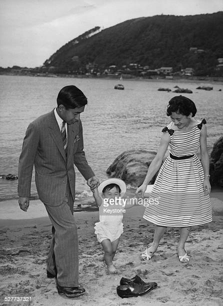 Prince Hiro walking on the beach near the Hayama Imperial Villa, Japan, with his parents, Crown Prince Akihito and Princess Michiko, 29th June 1961.