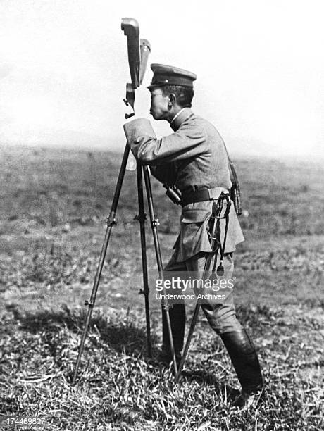 Prince Hirohito looking through the range finder at military maneuvers in Japan, December 6, 1922.