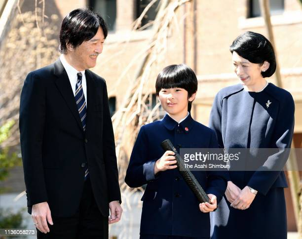 Prince Hisahito poses for photographs with his parents Prince Akihito and Princess Kiko of Akishino after attending the graduation ceremony of...