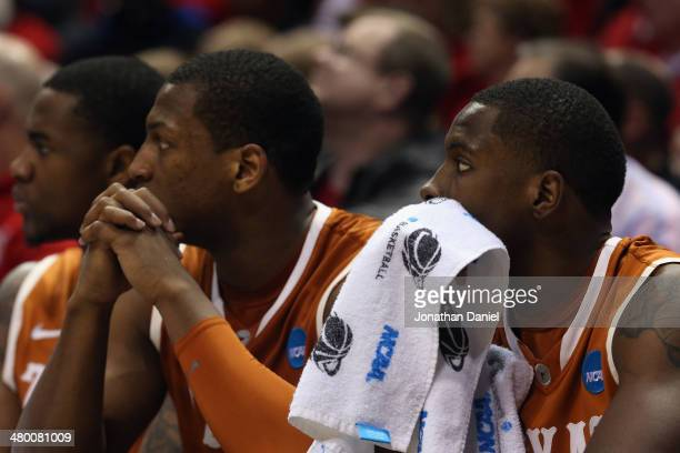 Prince Ibeh Jonathan Holmes and Kendal Yancy of the Texas Longhorns look on from the bench against the Michigan Wolverines during the third round of...