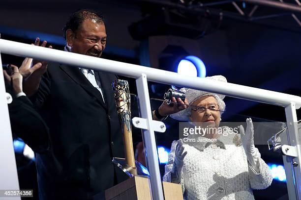 Prince Imran the CGF President attempts to retrieve the message from the baton as he presents it to Queen Elizabeth II Patron of the CGF during the...