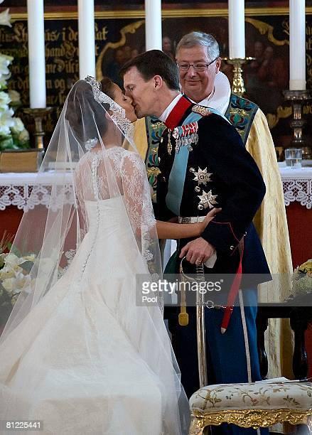 Prince Joachim of Denmark kisses his bride, Marie Cavallier of France, as Bishop Erik Normann Svendsen looks on at their wedding in Mogeltonder...
