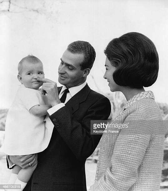 Prince Juan Carlos carrying his 18 month old daughter Elena standing next to his wife Sofia of Greece on May 25 1965 in Spain