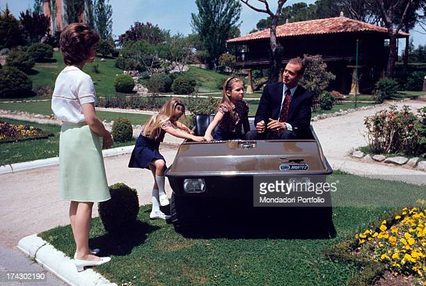 Prince Juan Carlos of Bourbon the future king of Spain on an armoured car next to his daughters Elena and Cristina in the garden of his villa La...