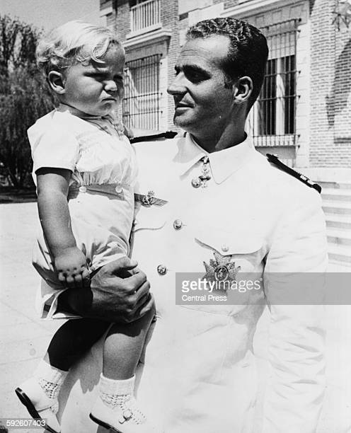 Prince Juan Carlos of Spain wearing military uniform as he holds his son Felipe in his arms, pictured following the announcement of his succession to...