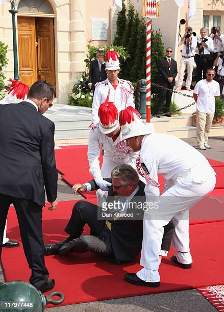 Prince Laurent of Belgium is helped to his feet after falling over as he attends the religious ceremony of the Royal Wedding of Prince Albert II of...