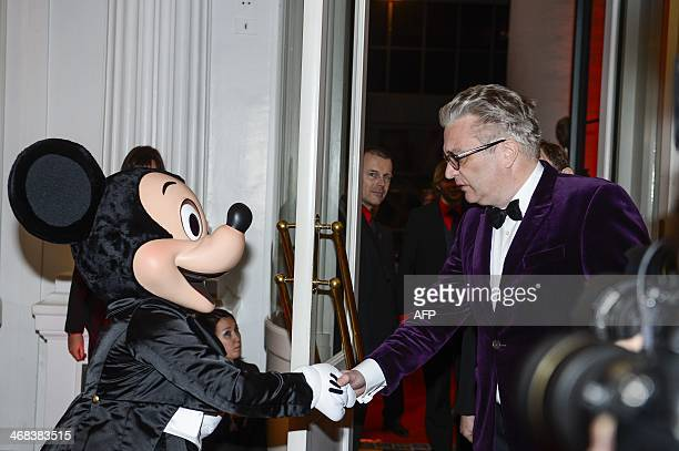 Prince Laurent of Belgium shakes hands with a man disguised as Mickey Mouse at the Belgium premiere of Disney film 'Saving Mr Banks' on February 10y...