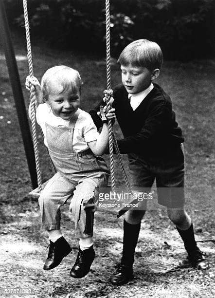 Prince Laurent sits on a swing that pushes his brother Prince Philippe in the park of the Belvedere castle in 1966 in Brussels Belgium