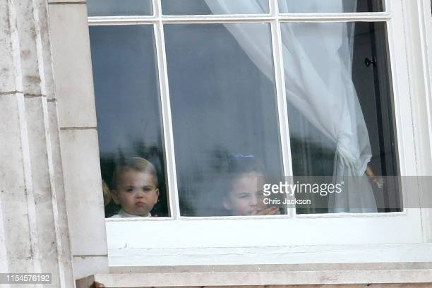 Prince Louis and Princess Charlotte peer out of the windows of Buckingham Palace during Trooping The Colour the Queen's annual birthday parade on...