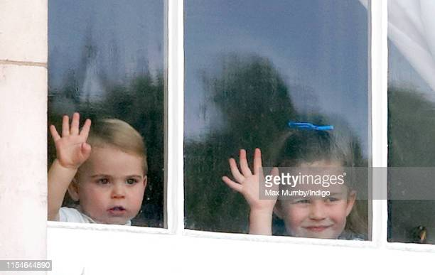 Prince Louis of Cambridge and Princess Charlotte of Cambridge wave from a window of Buckingham Palace as they attend Trooping The Colour, the Queen's...