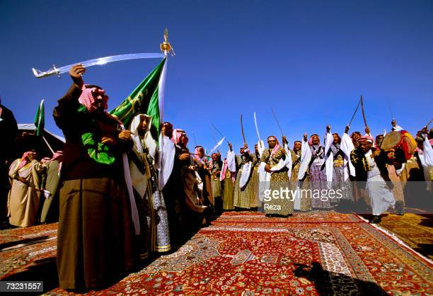Prince Mishaal bin Abdulaziz Al Saud wrapped in the Saudi flag and Al Saud princes perform the traditional Bedouin war dance using swords called the...