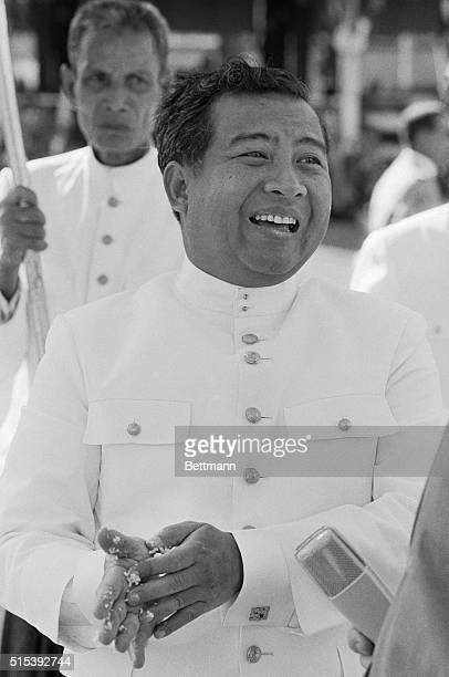 Prince Norodom Sihanouk of Cambodia wipes rice from his fingers after making a gift to Buddhist monks at a Phnompenh temple recently during the...