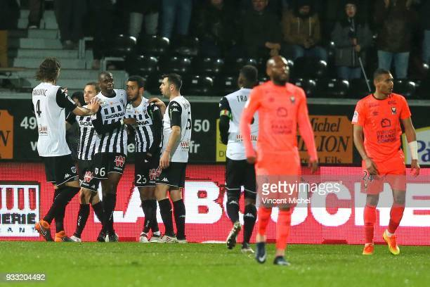 Prince Oniangue of Angers jubilates with teammates after scoring the third goal during the Ligue 1 match between Angers SCO and SM Caen at Stade...