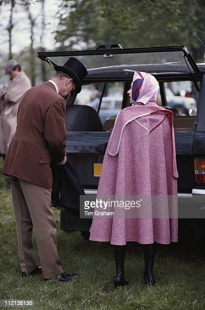 Prince Philip and Queen Elizabeth II wearing a pink cape at the Royal Windsor Horse Show held at Home Park in Windsor Berkshire England Great Britain...
