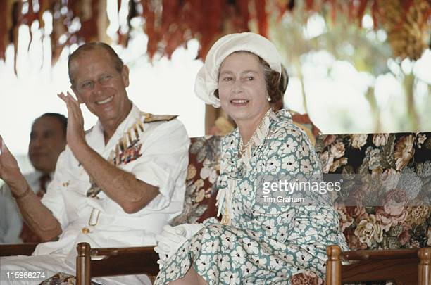 Prince Philip and Queen Elizabeth ll wearing hat designed by miliner Frederick Fox smiling as they are entertained in Tuvalu as part of their tour of...