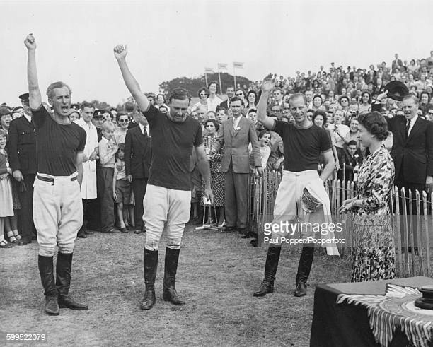 Prince Philip Duke of Edinburgh calls for three cheers from the crowd for his polo team as they are presented with the Invitation Cup by his wife Her...