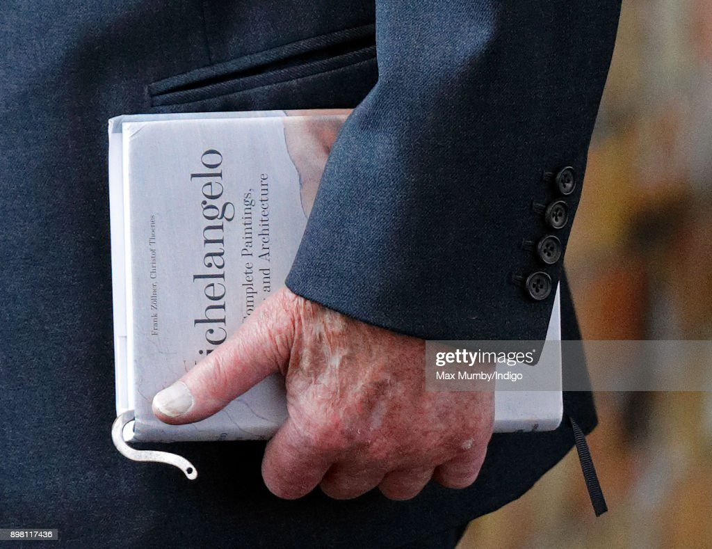 Prince Philip, Duke of Edinburgh carries his book 'Michelangelo: The Complete Paintings, Sculptures and Architecture' as he and Queen Elizabeth II arrive at King's Lynn station, after taking the train from London King's Cross, to begin their Christmas break at Sandringham House on December 21, 2017 in King's Lynn, England.