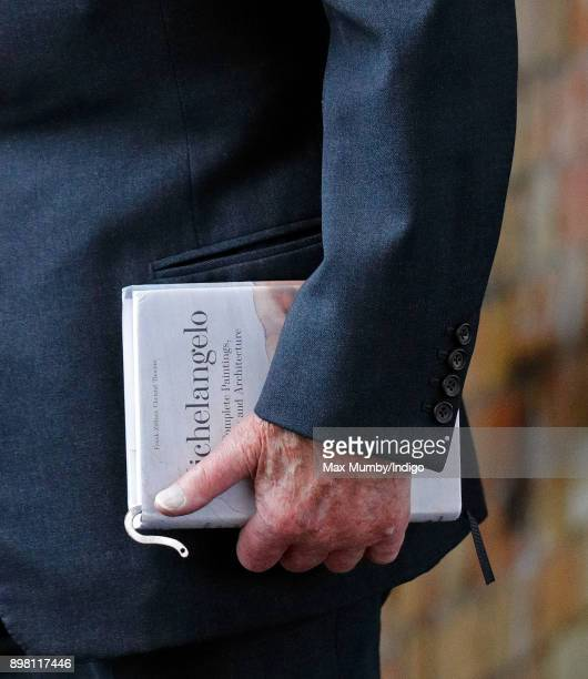 Prince Philip Duke of Edinburgh carries his book 'Michelangelo The Complete Paintings Sculptures and Architecture' as he and Queen Elizabeth II...