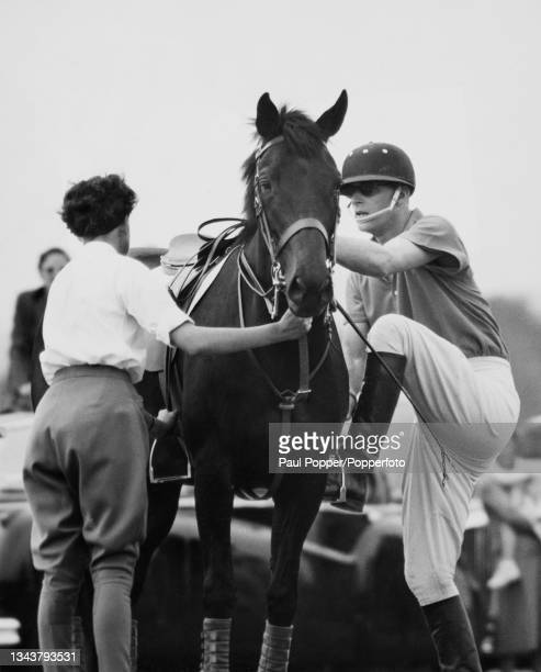 Prince Philip, Duke of Edinburgh climbs in to the saddle to play for the Cowdray Park team in a polo match against Friar Park at Midhurst in West...